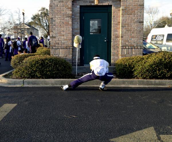 A drum major stretches out before the parade begins. In New Orleans students compete to lead their school bands.