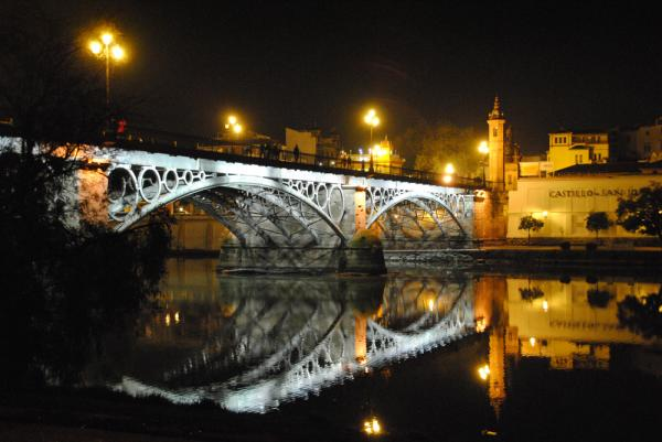 The Triana Bridge at night in Seville, Spain.
