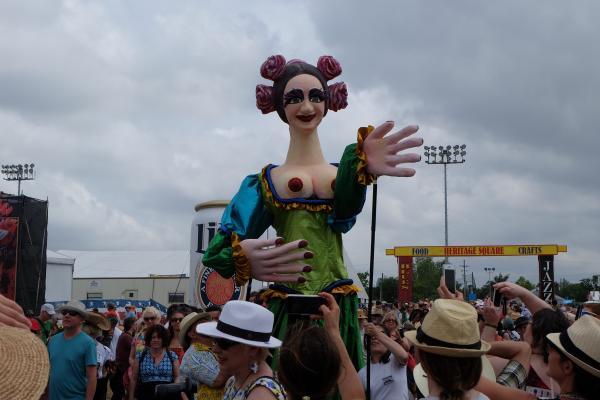 A giant puppet parade entering into the Casa Do Brasil area.
