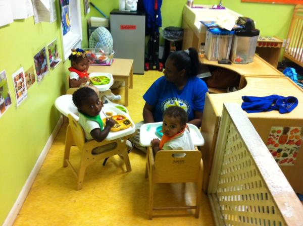 The babies at New Orleans' Kids of Excellence child care center sit down for meal time.