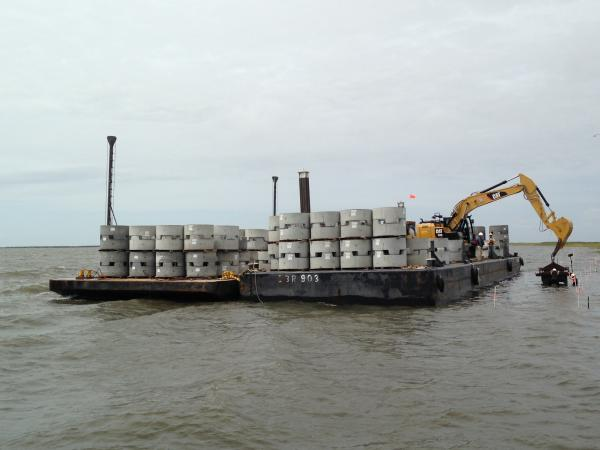 Concrete oyster beds wait to be offloaded into St. Bernard's Lake Athanasio