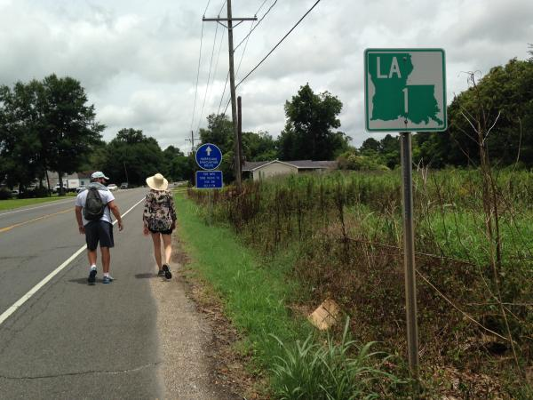 Kirk Green and Jenna DeBoisblanc walk along LA 1 towards Baton Rouge.