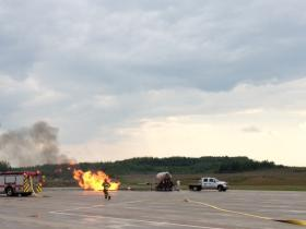 Fire crews work to put out a simulated fire the runway at the Rhinelander Airport.