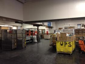 The warehouse of the Rhinelander Post Office is full of boxes and rolling carts.