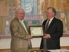 Mayor Dick Johns(L) receiving Earth Day designation from state USDA Director Stan Gruszynski(R) in the city council chambers.