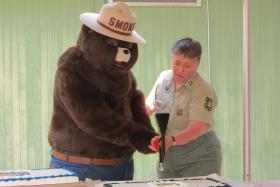 Smokey Bear gets some help cutting his birthday cake with a pulaski, a firefighter's tool.