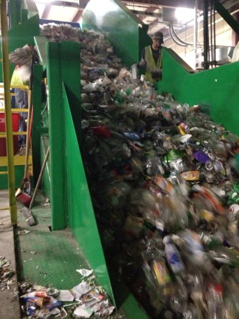Plastic bottles head up a conveyor belt to be crushed into bales.