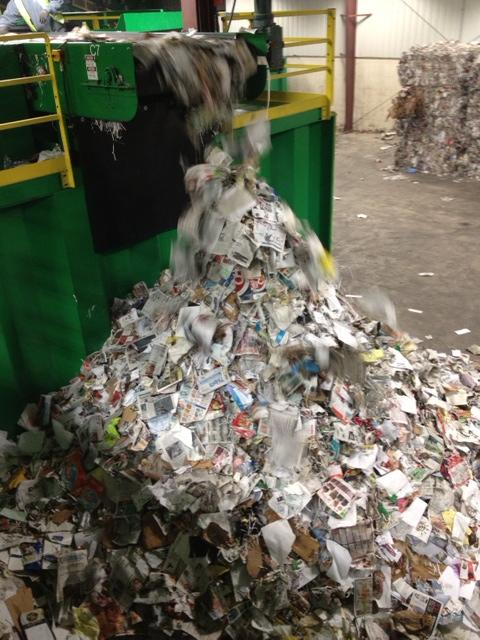 Sorted paper is poured into a pile for the next step of the process.