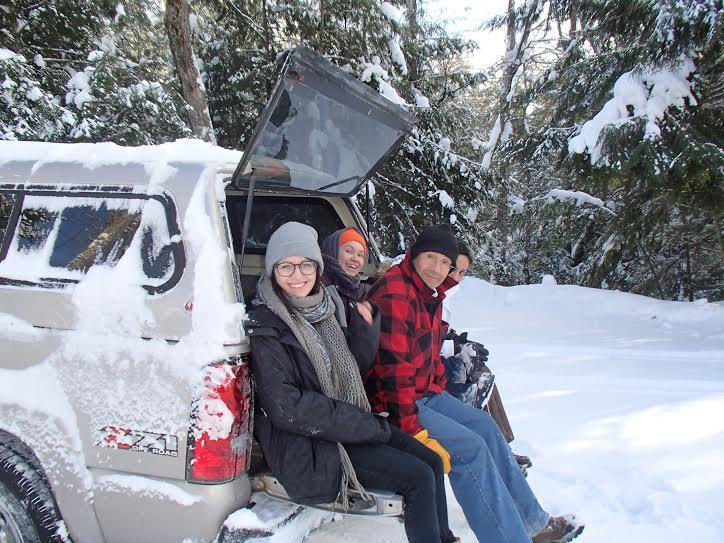 Professor Murru and several students sit on the tailgate to help the truck get up a slippery hill.