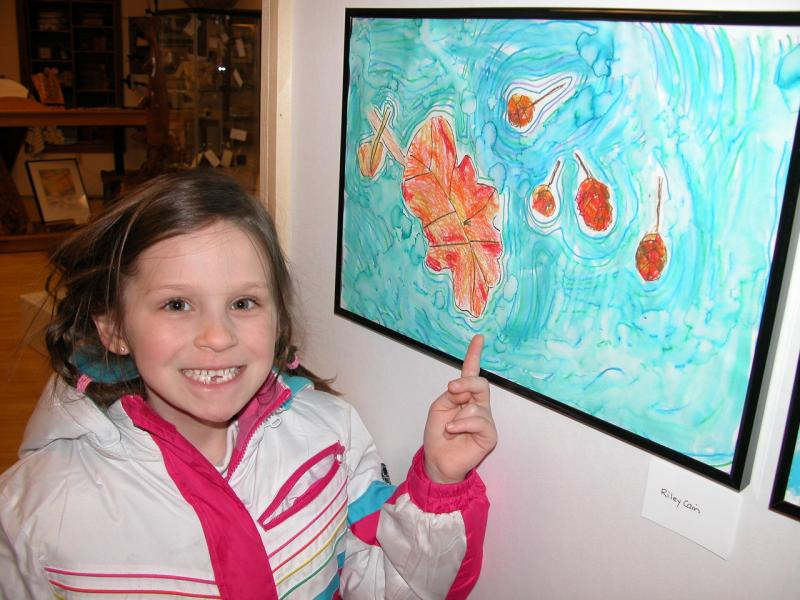 Artist Riley Cain points to her work displayed at the Land O Lakes Area Artisans gallery.