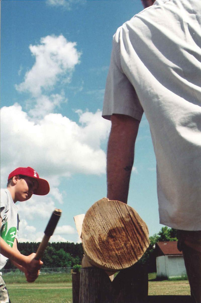 Eleven-year-old AJ pounds a black ash log, as Jarrod Stone Dahl steadies it.