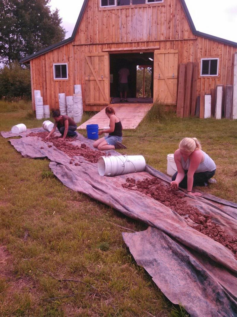 Artists prepare clay, dug from an onsite clay pit, for ceramics workshops.