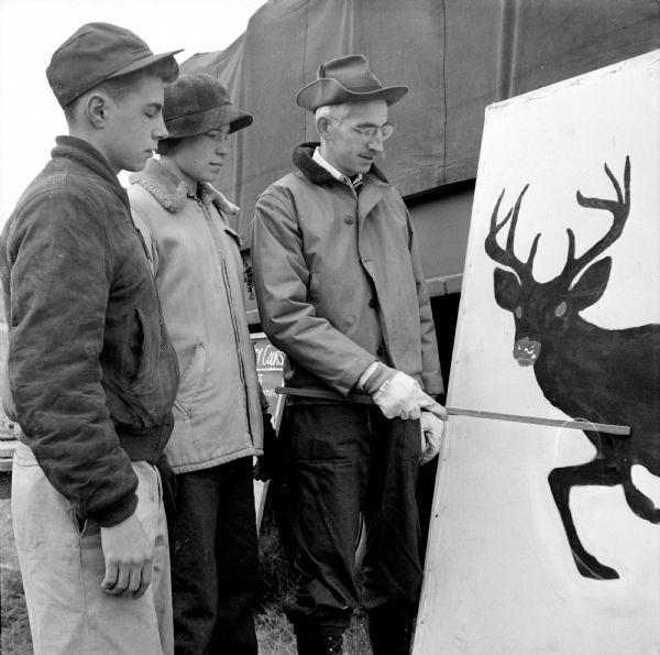 Two youthful hunters watch an instructor point out the vital points a hunter must hit to get his buck at a training course in gun safety held at the Winnequah Gun Club near Lodi in 1953.