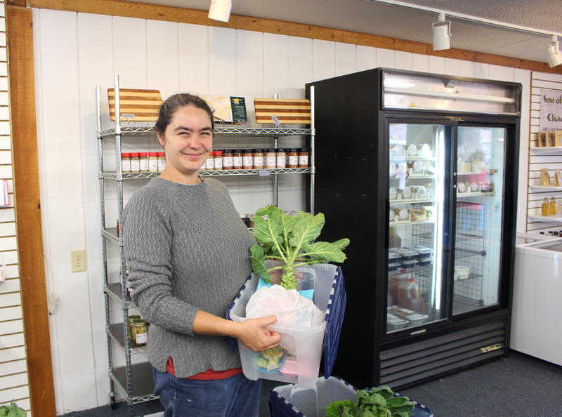 Jasmyn Schmidt holding one of the North Woods Farm Share boxes at Hillbilly Hollow in Eagle River.