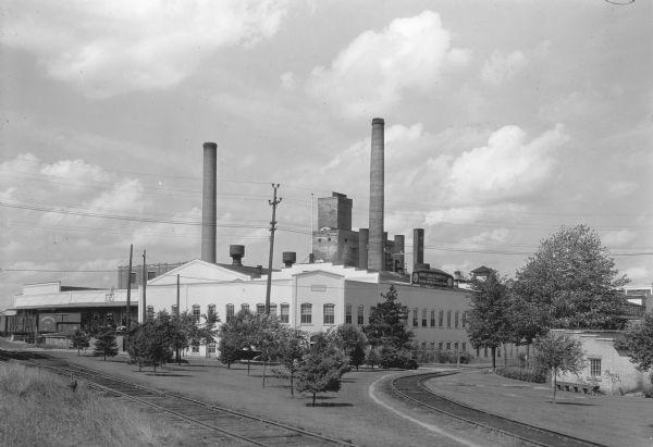 Two large smokestacks rise from the 1903 building of the Rhinelander Paper Company. Railroad tracks are crossing the left foreground diagonally; a second set of tracks are curving off to the right.