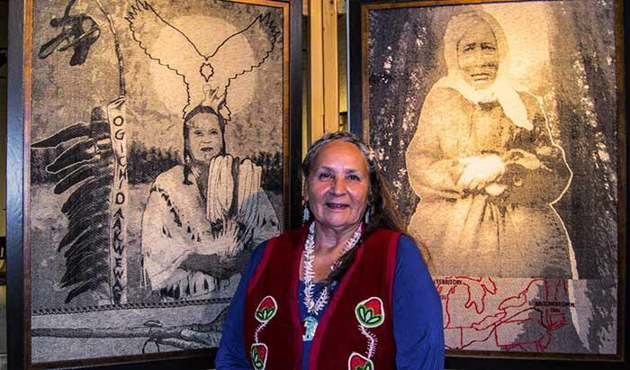 Tinker Schuman from the Lac du Flambeau Band of Lake Superior Chippewa Indians stands next to the weaving Mary Burns did of her as part of the original Ancestral Women Exhibit (left).