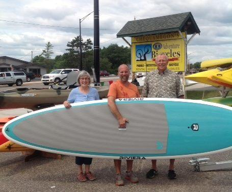 Andrew Teichmiller, owner of Chequamegon Adventure Company, with paddleboard winners, Karen and Bob Turnquist.