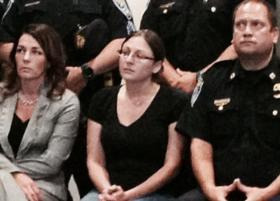 Officer Daryl Pierson's wife, Amy, sitting in between members of the Rochester Police Department.