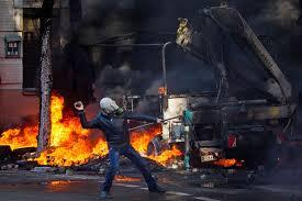 Demonstrator throws a rock during clashes between opposition protestors and riot police