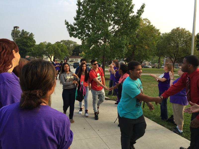 Teachers and volunteers shake hands with high schoolers.