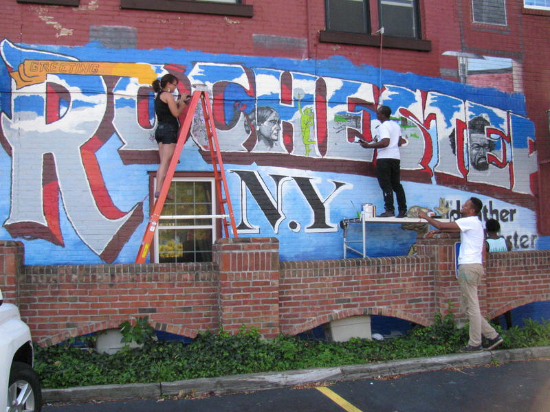 """Karina Sáez-Bula, David Johnson (on scaffold), Shawn Dunwoody, and Ephraim Gebre, left to right, work together on the """"Rochester"""" mural."""