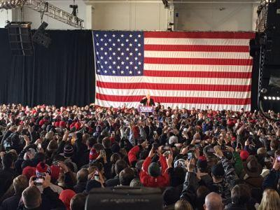 Donald Trump speaks to the mass gathering at an airplane hangar.