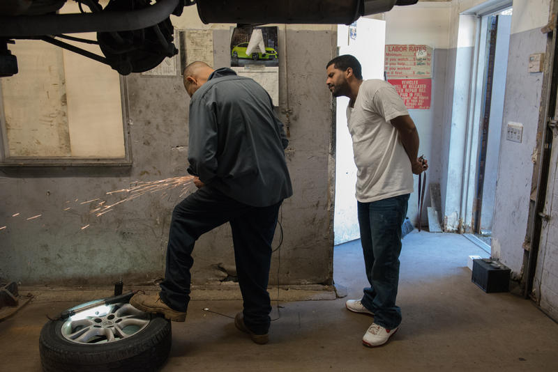 """Israel Garcia, 49, of Rochester works at Dalbert's Auto Shop while a customer watches. """"A $15 minimum wage would not only help me but a lot of people."""""""