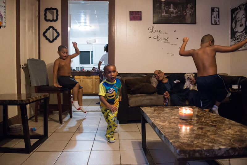 "Israel Garcia relaxes at his home in Rochester, N.Y., with his grandchildren, from left, 5-year-old Devon, 3-year-old Zaiden and 7-year-old Jeremiah. He said he wants his grandchildren to be ""hard-working and fighters."""