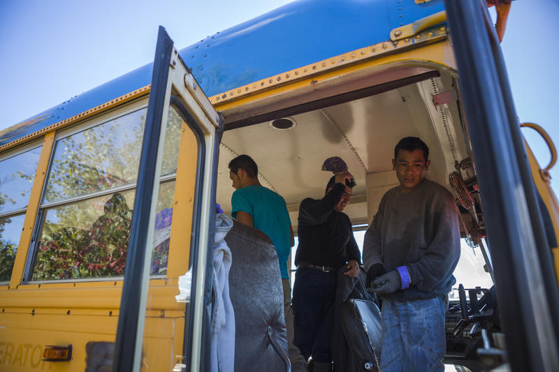 """Migrant workers board the bus that shuttles them between fields at Root Brothers Farm in Albion. """"We pay their transportation, we pay their meals on the way up, we pay their transportation home,"""" said Robin Root, farm co-owner."""