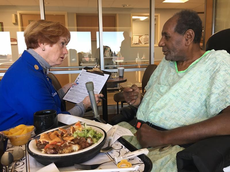 Volunteer Peggy Ghysel asks John Cotton information for his absentee ballot application at Rochester General Hospital.