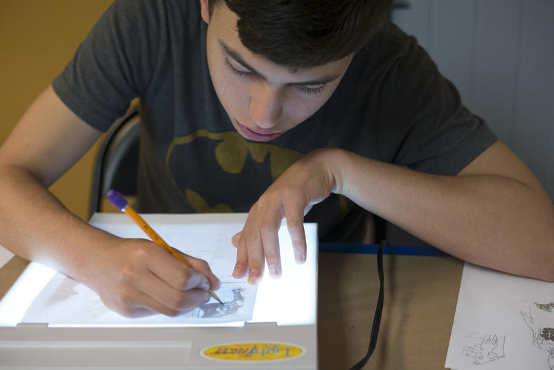 Nate enjoys tracing drawings using a light box.