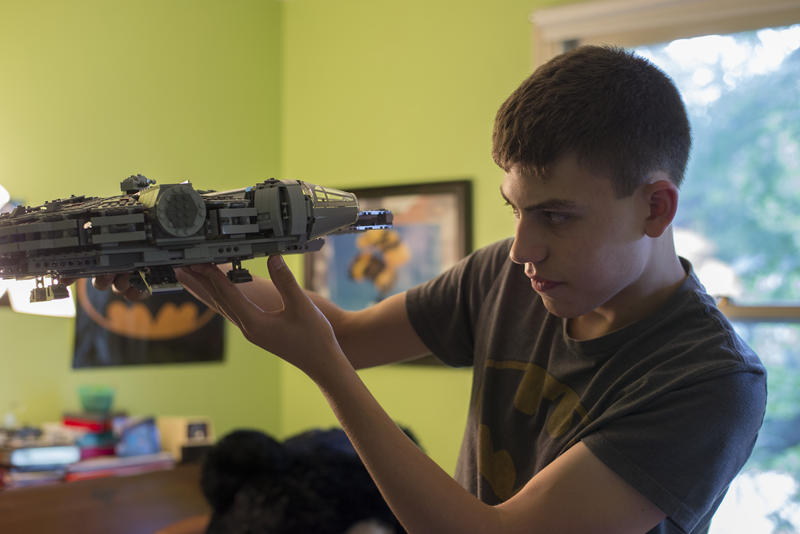 Nate looks at a model in his room in his Pittsford home.