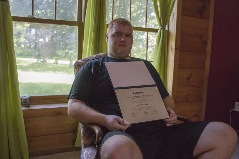 Jesse shows the certificate he received after completing the LIVES program at the State University of New York at  Geneseo. Jesse's father, Dwayne, said the program helped his son grow academically and socially.