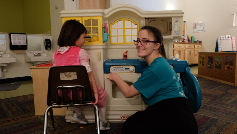 "Maggie McCrumb plays with a child at a day care center while being assessed by a ""vocational evaluator,"" in order to get help with job placement from New York state."