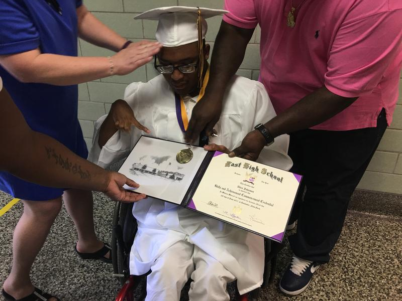 Akin Johnson holds his credential during the East High School commencement in June.