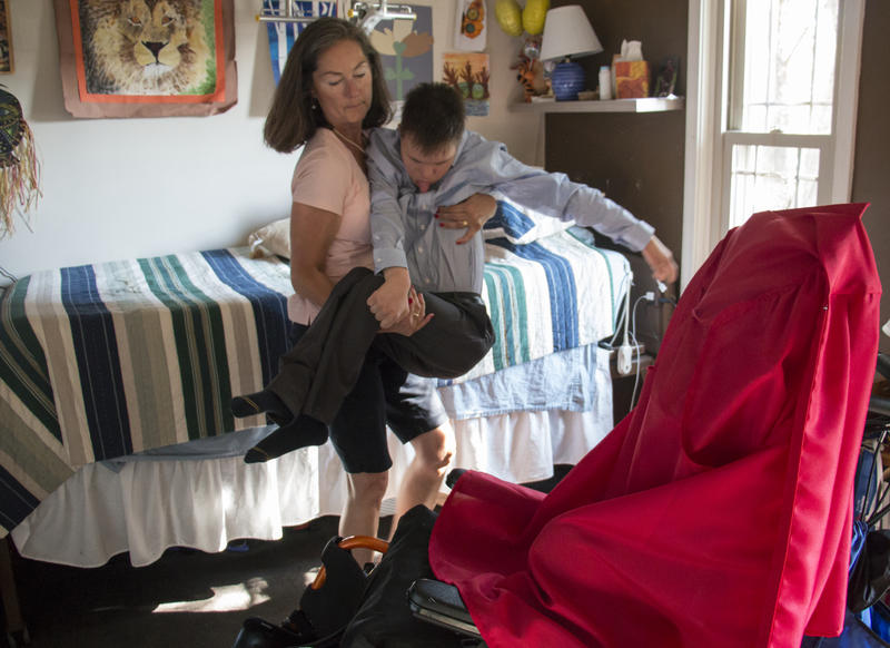 Barbara Jackson carries her son Jonathan to his wheelchair as they prepare for his graduation ceremony.