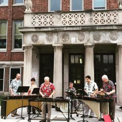 RPO Marimba Band playing outdoors in front of a building
