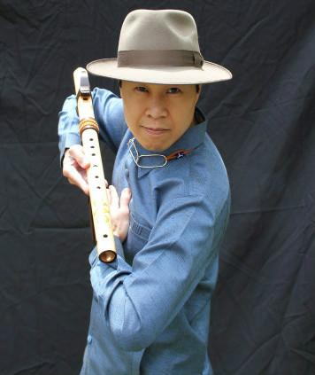 Dr. Jefferson Svengsouk wearing a hat and holding a Native American flute