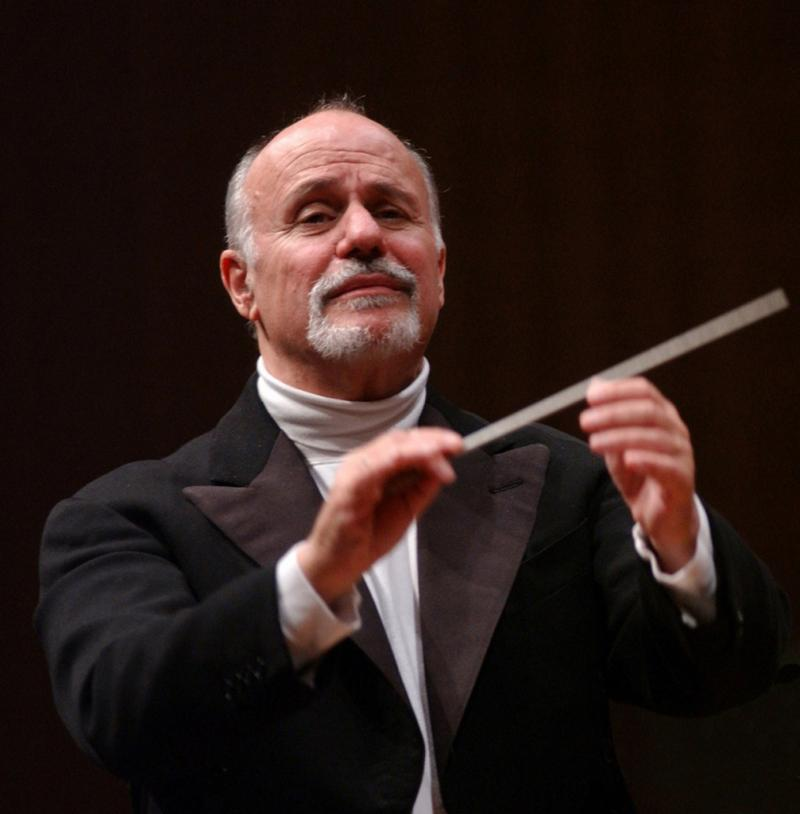 David Zinman conducting with baton, wearing black jacket and white turtleneck