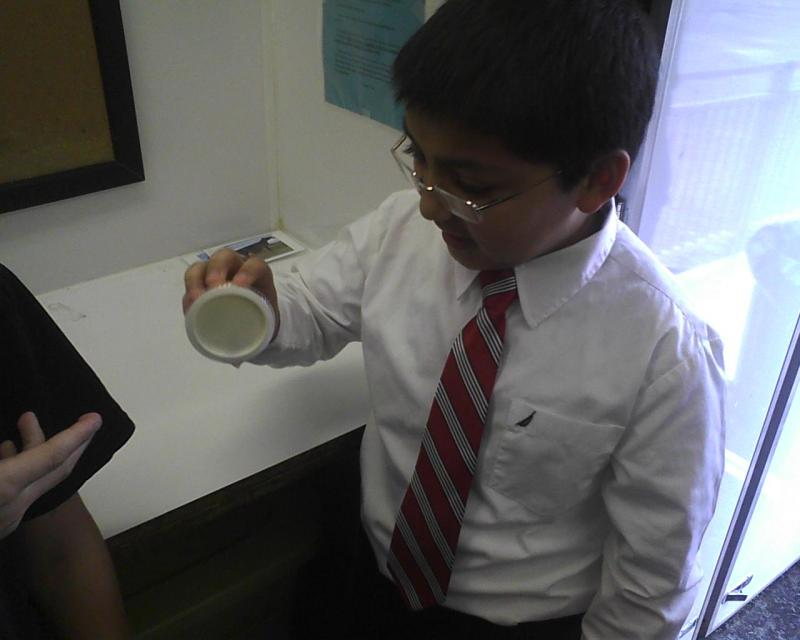 Ridgley Middle School sixth-grader Armand Farazdaghi is making butter during a hands-on science class in the Mobile Agriculture Science Laboratory this week.