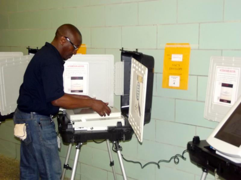 Election Technician Tommy Cozart makes a final inspection on a voting machine.