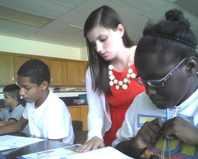 Holabird Middle School first-year teacher Danielle Miller helps students with an in-class science assignment.