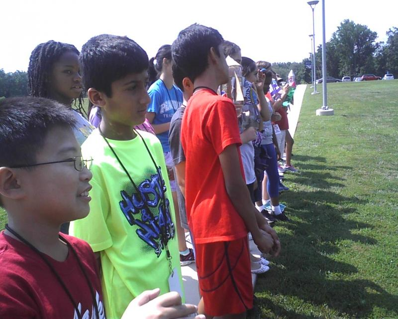 Students line up on the grounds of the APL as they wait their turn to launch rockets that they designed using water bottles, cardboard and water.