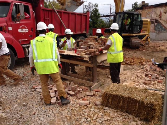 Workers processing the brick.  Processing involves chisleing the mortar off of the brick.