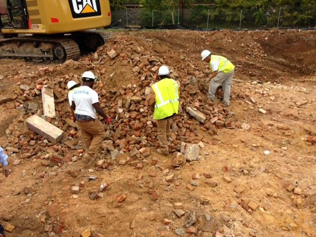 Workers try to find bricks in the dirt.
