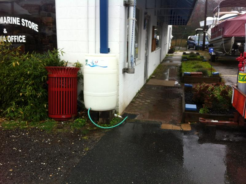 The marina installed rain barrels to catch rain coming off the roof. The barrel has a hose at the bottom. The water collected is used for things like watering plants.