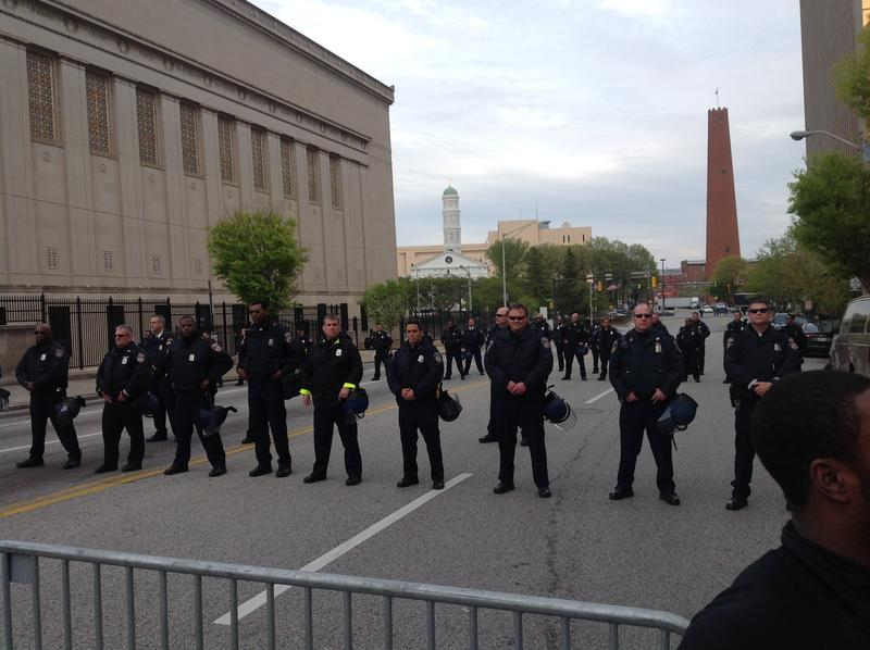 Baltimore Police officers standing in line at North Gay and Fayette Streets watching protesters pass.