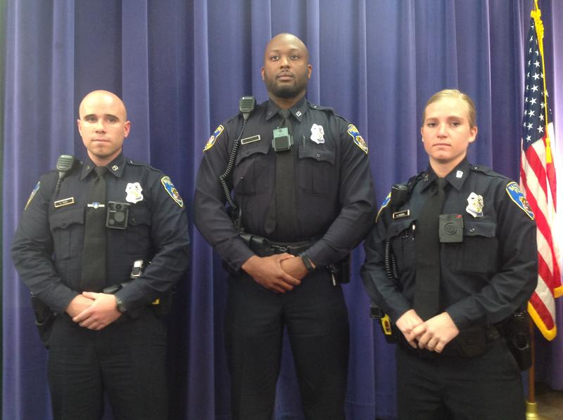 Police Officers (from left) Gregory Twigg, Alan Chanoine and Hannah Parrish modeling the body cameras that will be tested during a 54-day pilot program.