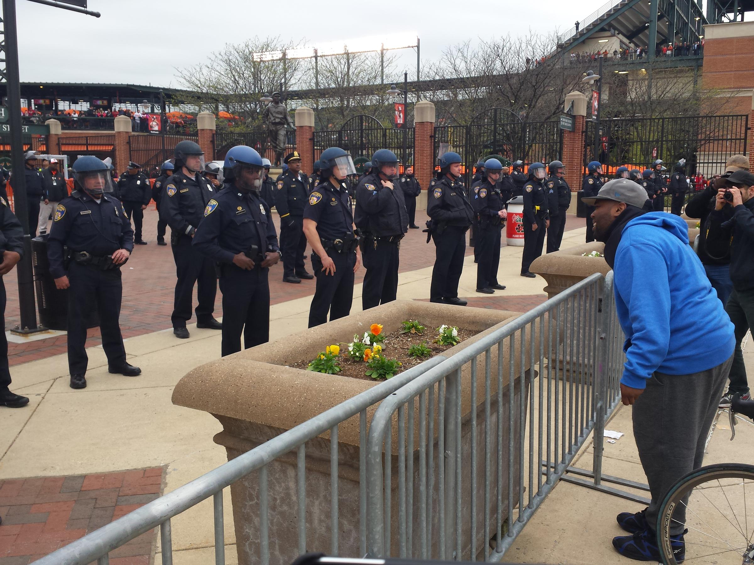 Baltimore police officers in riot gear push protestors back along - A Protester Heckling Baltimore Police Officers At Oriole Park At Camden Yards