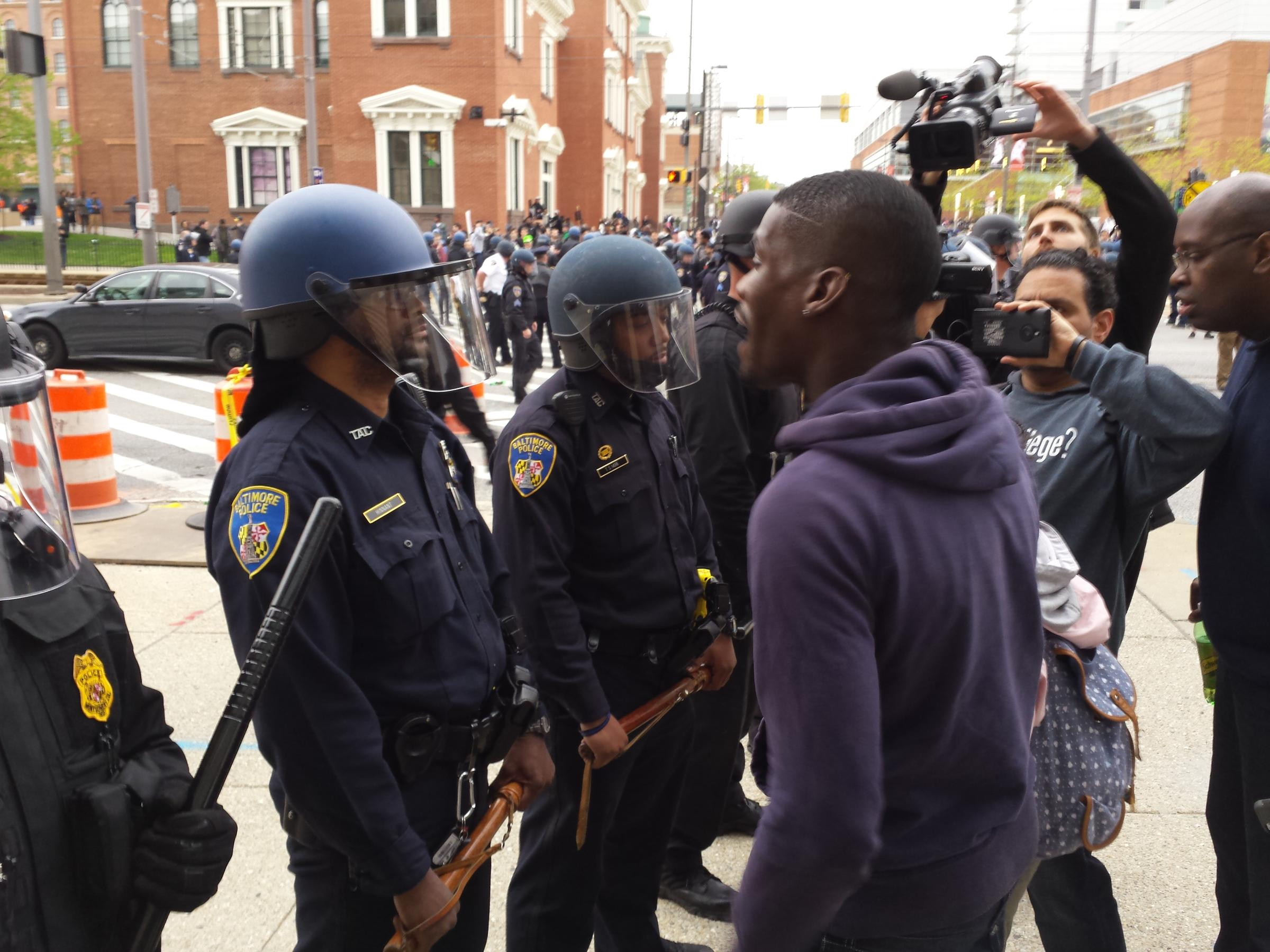 Baltimore police officers in riot gear push protestors back along - A Protester Heckling A Baltimore Police Officer At Howard And Camden Streets